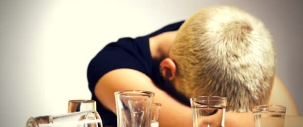 woman with head down drinking alcohol