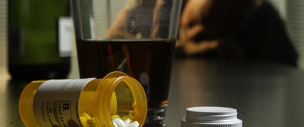 pill bottle and alcohol on table with sick man behind
